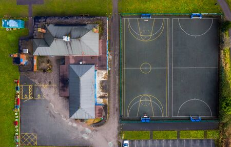 Aerial view of a childrens playground with a basketball and football court next to each other shot from above looking straight down