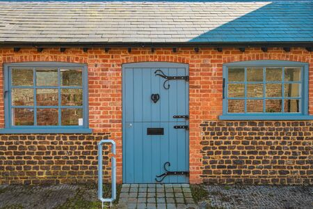 Small brick cottage in village in Southern England during Summer with Blue windows and wooden door 免版税图像