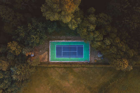 Aerial drone view of Tennis Court hidden away behind a tree line during a summer sunset in the hills of Surrey, England, UK