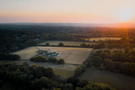 Aerial shot of farmland and house surrounded by woodland in Surrey, UK. Sunset