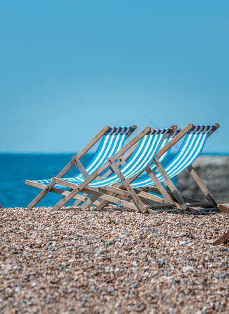 Blue and White Striped Deck Chairs at Brighton Pebble Beach in UK Summer 2020