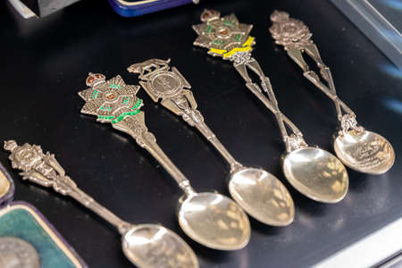Aldershot, UK - 5th September 2020: A row of silver and brass ceremonial military spoons on display in army museum 新闻类图片