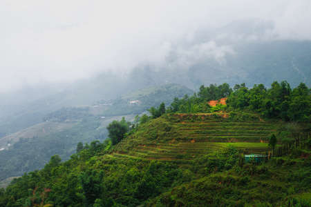 Famous Rice terraces with a building on top with mountains and clouds in the background. Sapa, Northern Vietnam October 2019
