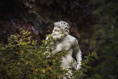 White statue sculpture of Pan the Greek god with a flute in his hand hiding behind foliage looking cheeky