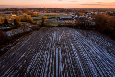 Aerial view of Frozen ploughed field with beautiful orange sky in the background, late sunset in Winter