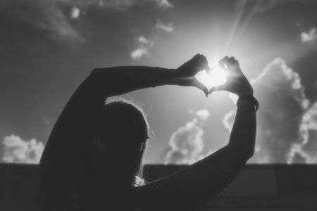 siluet: Black silhouette of a girls show by hands a figure of the heart from summer sun Stock Photo