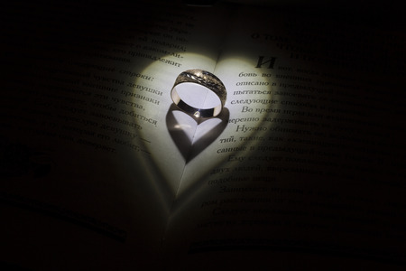 brak: Golden ring in the open book fall some shadow like a hearts