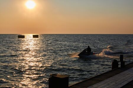 Silhouette of a man on the driving jet ski at the summer sunset