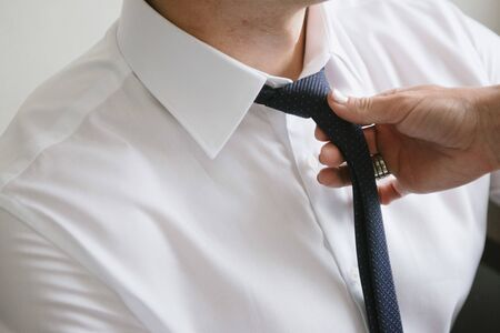 Woman tying a black tie around the neck of a man close up