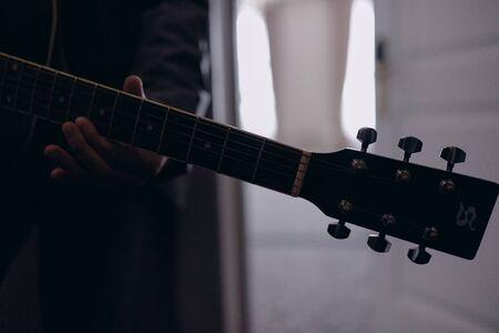 Man playing guitar indoors closeup