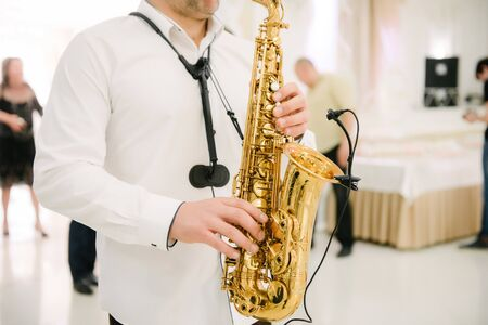 Musician playing saxophone indoors.Musician playing saxophone close up Stock Photo