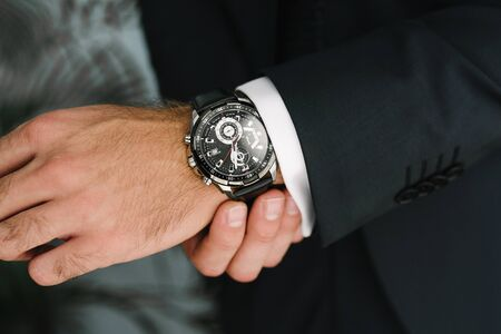A man in a suit adjusts the clock on his hand