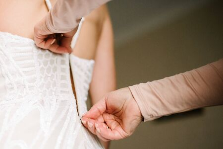 A white wedding dress is knitted to the bride. A bride is being helped to wear the wedding dress. The bride's preparation for the wedding Imagens
