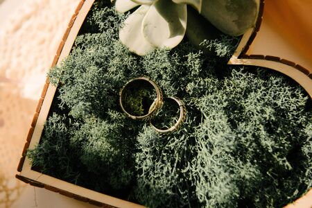 Wedding rings of the bride and groom are in a wooden box in the shape of a heart close-up