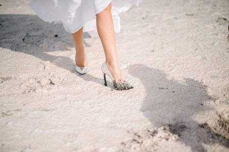 The legs of the bride in a wedding dress in shoes close op