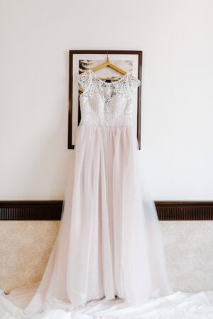 White wedding dress hanging in the bedroom. White bride dress close up