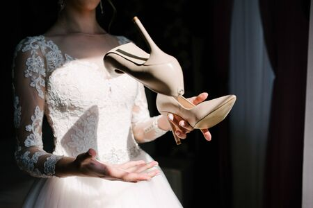 Bride in a white wedding dress holding wedding shoes