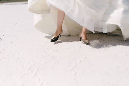 The legs of the bride in a wedding dress in shoes close op Stock Photo