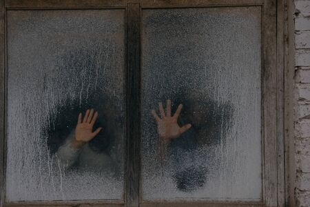 Male and female Hands on a misted window close up. Hand on a misted window