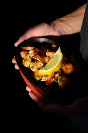 The waiter holds on a tray a dish with shrimps and a glass of beer