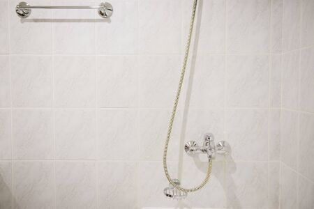 Steel hanging shower in a white marble bathroom close-up