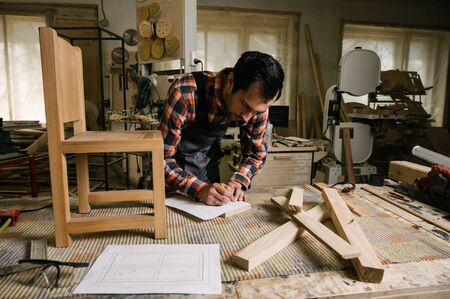Working process in the carpentry workshop.A man in overalls works in a carpentry workshop.Profession, carpentry, woodwork and people concept