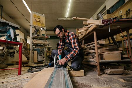 Working process in the carpentry workshop.A man in overalls works in a carpentry workshop.A man works on a circular saw.Profession, carpentry, woodwork and people concept