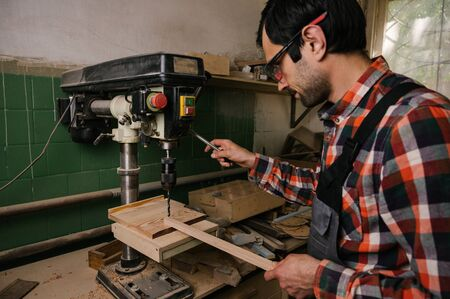 Working process in the carpentry workshop.A man in overalls works in a carpentry workshop.A man drills wooden board with a drilling machine.Profession, carpentry, woodwork and people concept