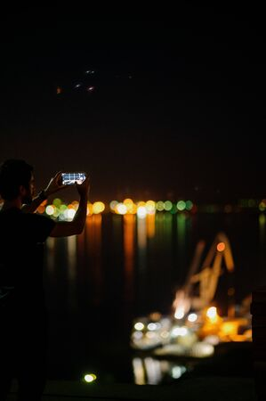 A man takes a photo of the night city on a smartphone.Shooting the city lights with a mobile device at night. View through the screen at the time a man takes a photo of a city at night. Cityscape