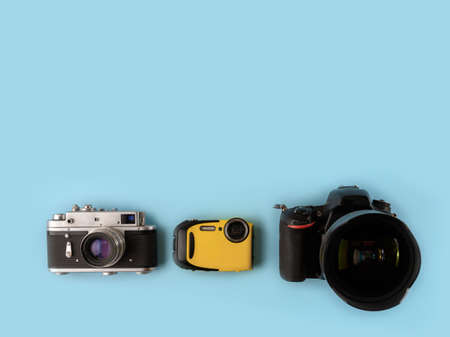 Camera evolution.Cameras of different types and generations on a blue background, top view, flat lay. Three cameras of different generations on a blue background. Technological progress of cameras