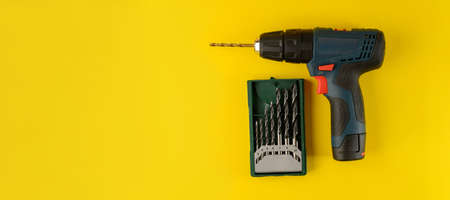 cordless drill, screwdriver with drill bit on yellow background, top view. Drill with drills of different types and sizes on a yellow background, flat lay