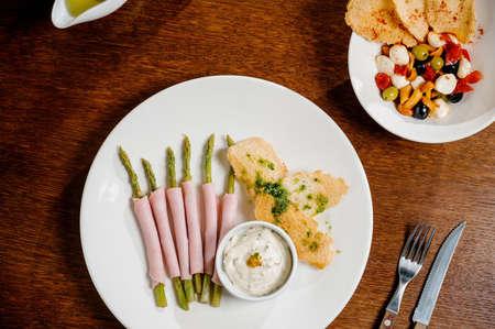 Fresh organic asparagus wrapped in Parma ham on wooden background Reklamní fotografie