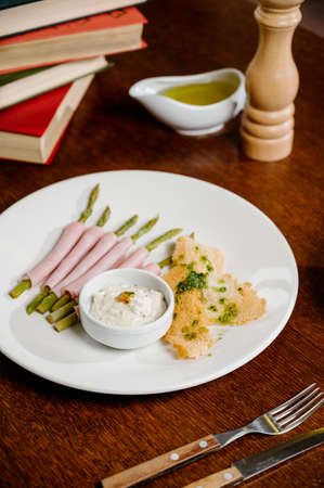 Fresh organic asparagus wrapped in Parma ham on wooden background