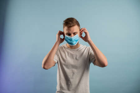 Young man tearing medical mask in studio. Removing mask, quarantine ends. Getting out of isolation