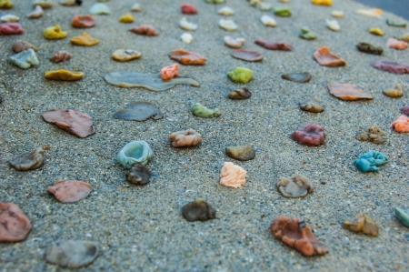 Multicolored gum stuck to cement