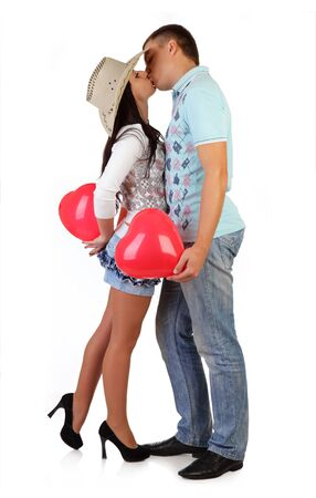 Young couple embraces, kisses and holds balloons - hearts isolated on a white background Stock Photo - 8422889