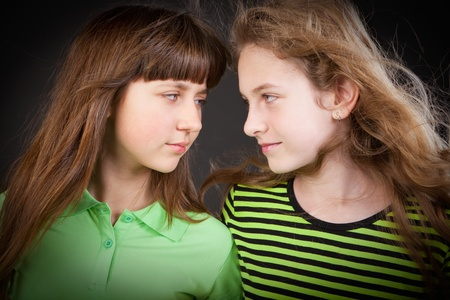 Portrait of two young beautiful girls in studio a dark background Stock Photo - 9779318