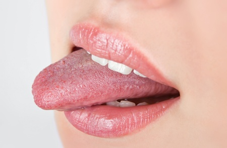 Beautiful woman leaking teeth with tongue close-up Imagens