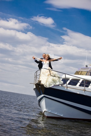 Happy bride and groom on a luxury yacht photo