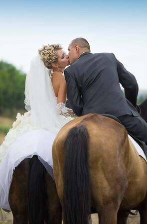 Bride and groom in forest on the horses and kisses photo