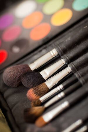 neutrals: cosmetic brushes. multicolored eye shadows with cosmetics brush Stock Photo