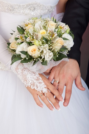 Bride and groom hands with wedding rings and bouquet of roses  Stock Photo