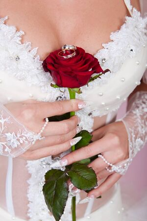 The bride holds in a hand a red rose with wedding rings. photo