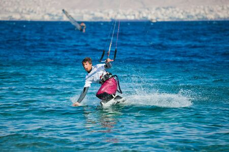 Kite surfing on the sea. The beautiful suntanned young guy goes for a drive on a board by the sea photo