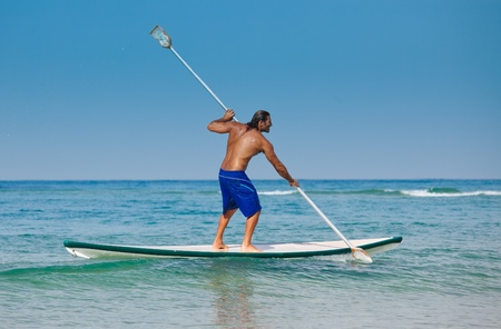 The guy with an oar on a surfboard. The beautiful brawny guy with an oar in hands on a surfboard.