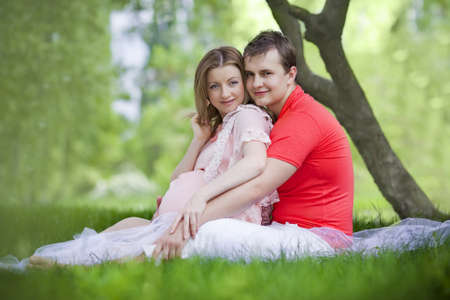 Husband and wife maternity expecting a child or baby posing in the park Stock Photo - 13600274