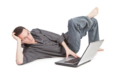 Young man lying on the floor working on his laptop Stock Photo - 13791496
