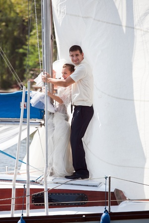 Happy groom and the bride on the yacht in solar and bright day photo