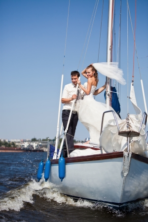 Happy groom and the bride on the yacht in solar and bright day Stock Photo