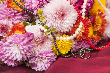 Colorful chrysanthemum and daisy flowers on a claret fabric with wedding rings and a beads photo